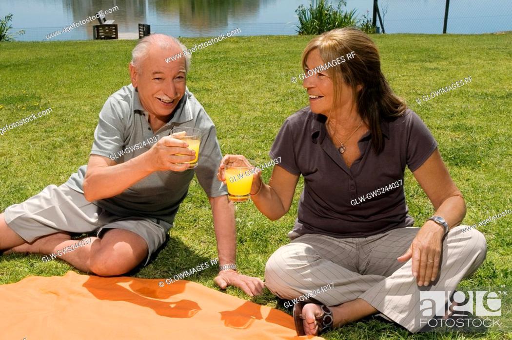 Stock Photo: Senior couple holding glasses of juice at picnic.