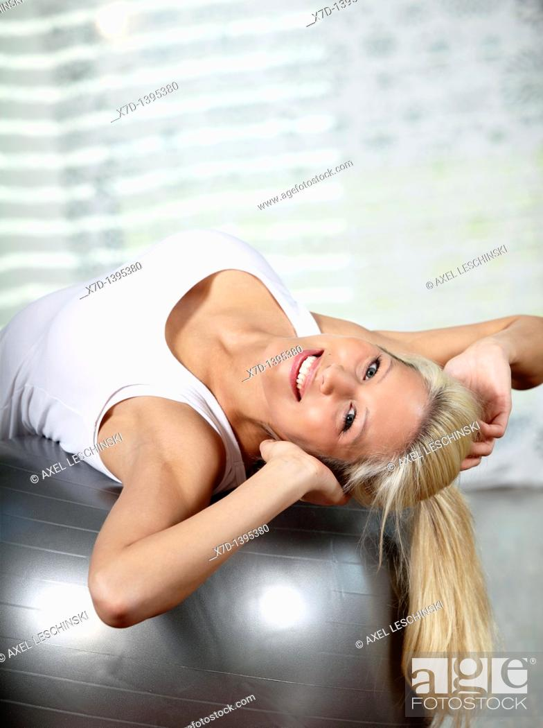 Stock Photo: young blond woman exercising with gymnastic ball.