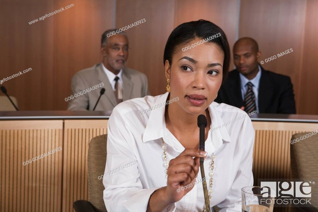 Stock Photo: African businesswoman speaking into microphone.