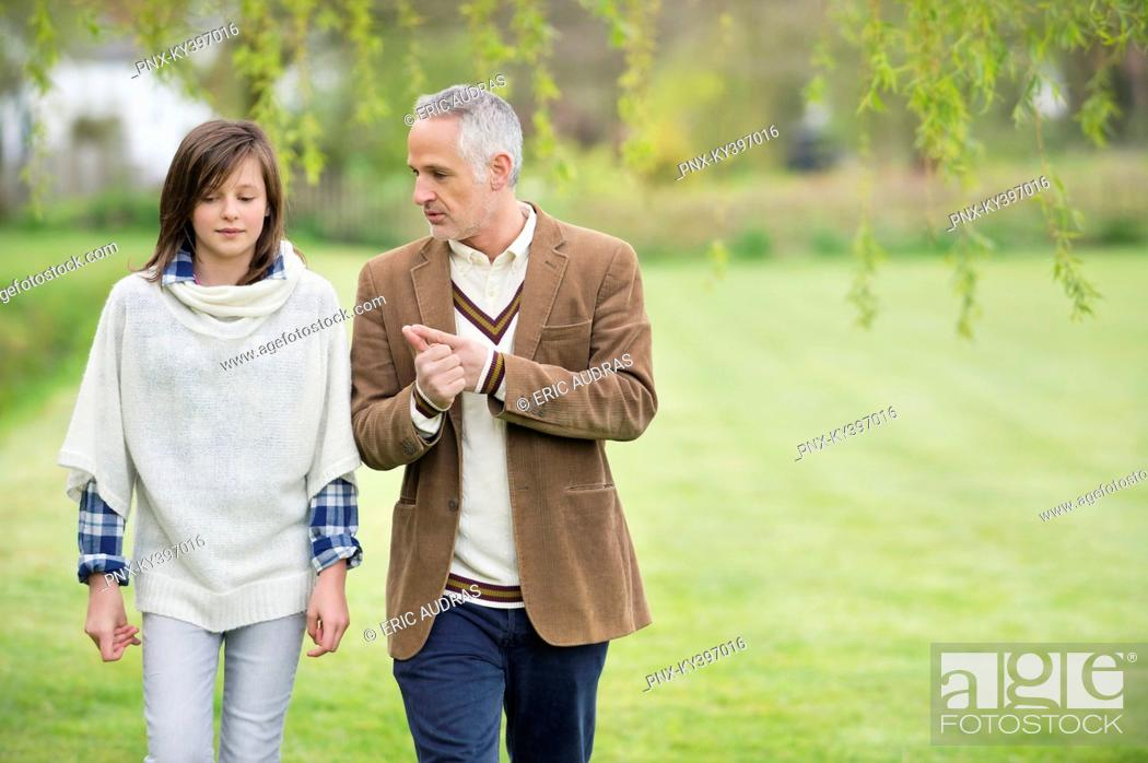 Stock Photo: Man discussing with his daughter during walk in a park.