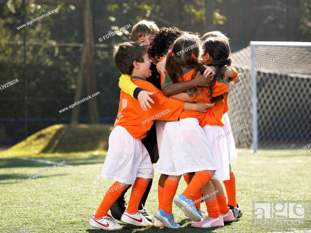 Stock Photo: Children in soccer uniforms hugging.