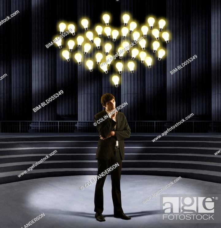 Stock Photo: European businessman standing under floating light bulbs.
