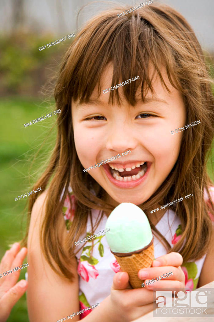 Stock Photo: Young Asian girl eating ice cream cone.