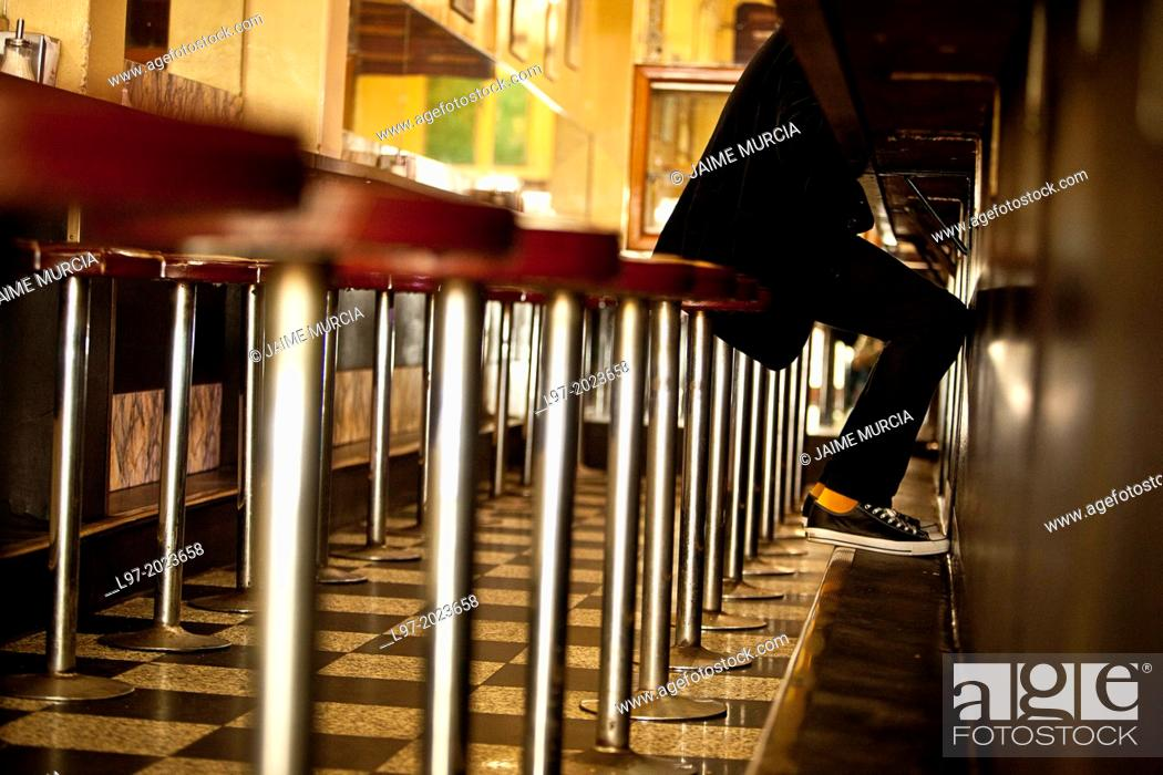 Stock Photo: A young man wearing sneakers sits on a bar stool in cafe, central Melbourne, Australia.