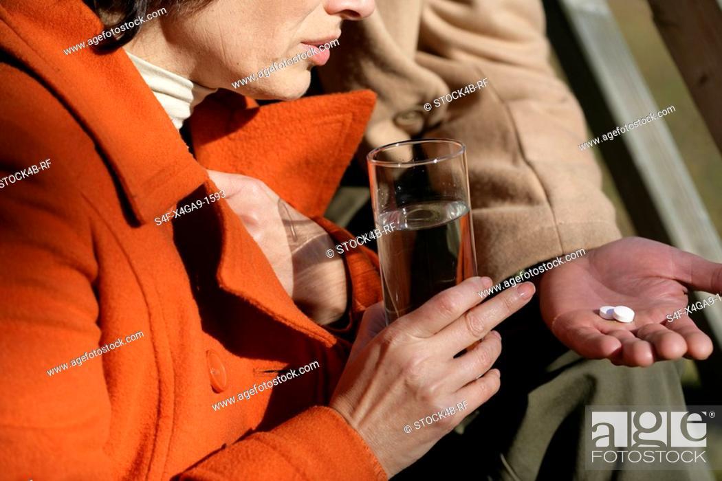 Stock Photo: Mature man handing his wife two pills.