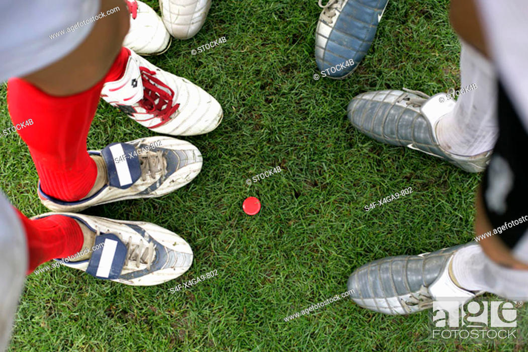 Stock Photo: Soccer players standing around a red chip.