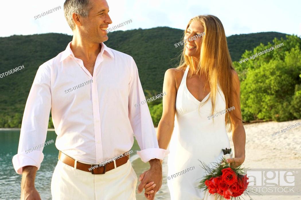 Stock Photo: Newlyweds walking on beach, St. John, US Virgin Islands, USA.