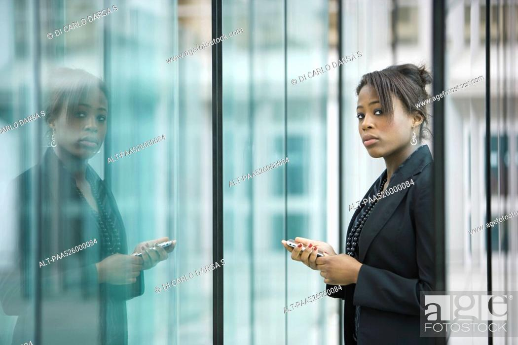 Stock Photo: Businesswoman using cell phone, looking at camera.