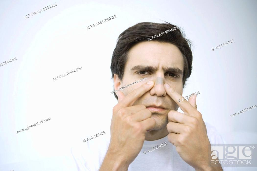 Stock Photo: Man applying adhesive bandage on his nose, looking at camera.