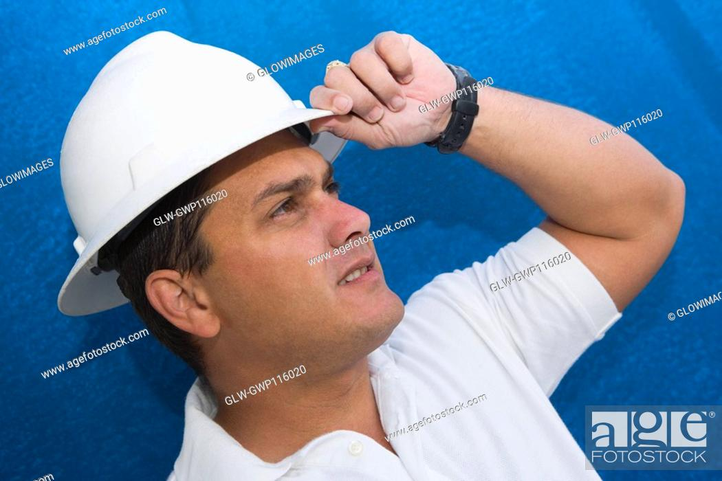 Stock Photo: Close-up of a male construction worker adjusting his hardhat.