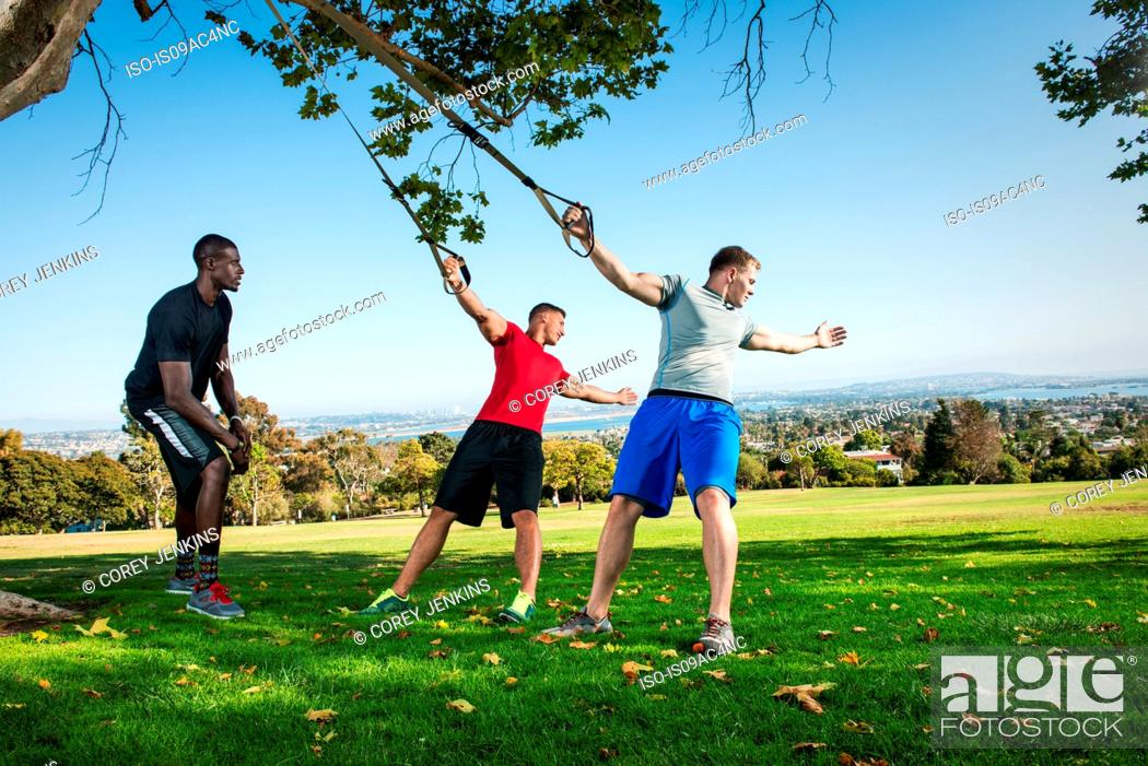 Stock Photo: Young men and trainer using lunge rope in park.