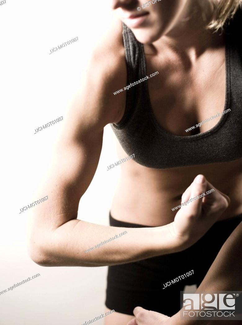 Stock Photo: Woman flexing biceps muscle.