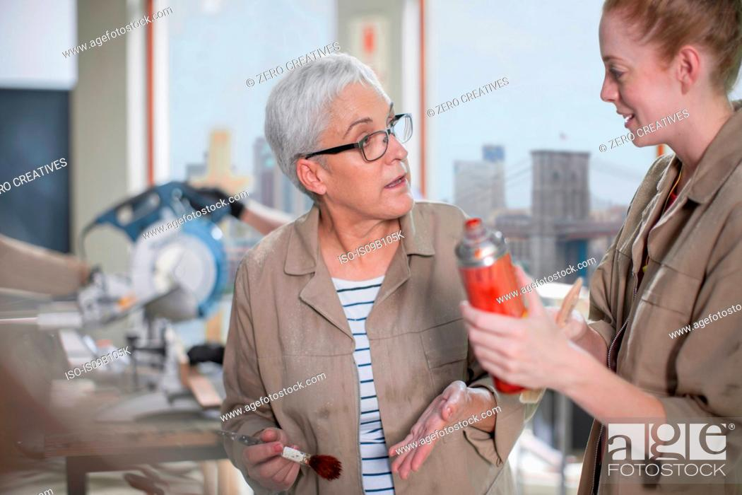 Stock Photo: Mature female carpenter explaining wood stain to trainee in furniture making workshop.