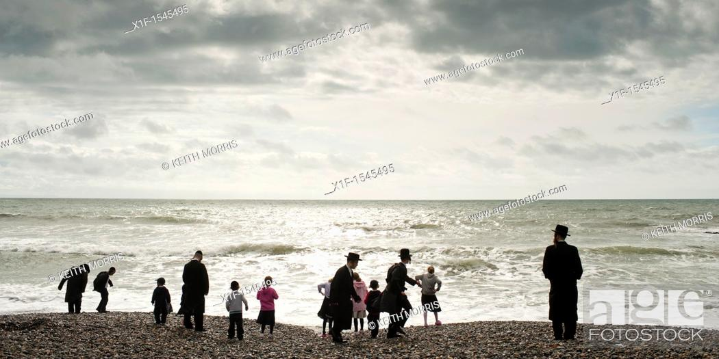 Stock Photo: Orthodox Hassidic jews on summer holiday on the beach at Aberystwyth Wales UK.