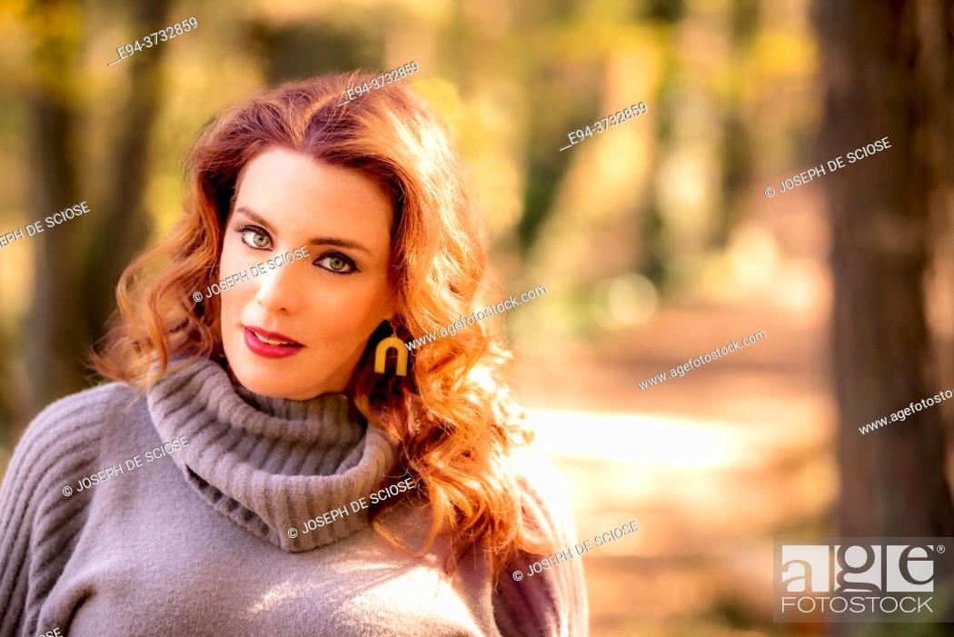 Stock Photo: A pretty 38 year old redheaded woman outdoors in a park setting in the autumn looking at the camera.