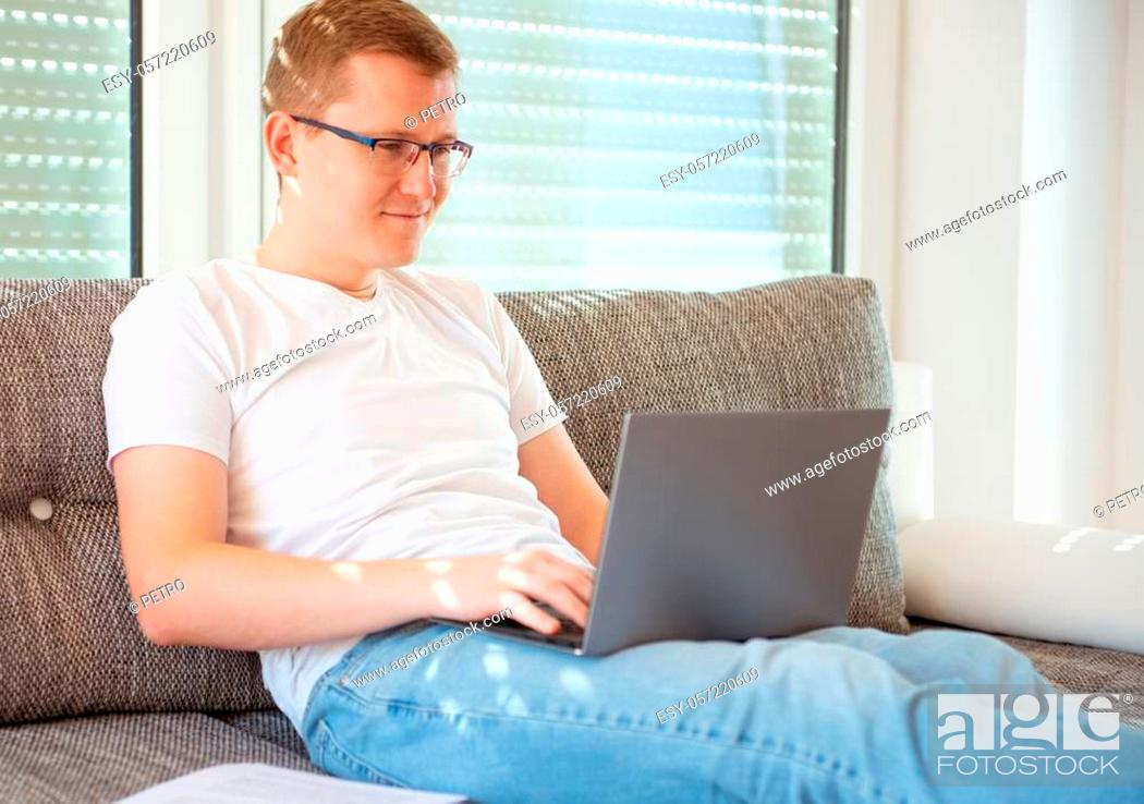 Stock Photo: Young male freelancer in white working with laptop at home.