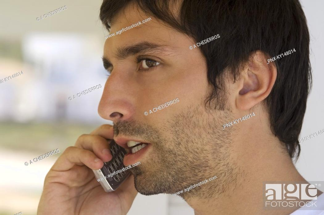 Stock Photo: Portrait of a young man using mobile phone.