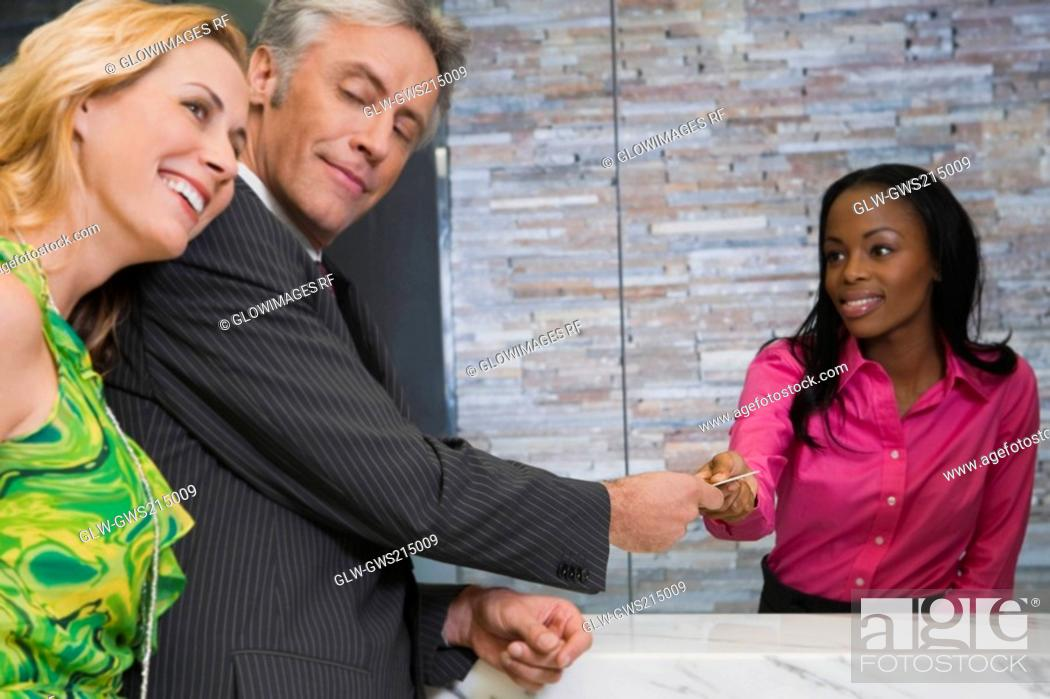 Stock Photo: Mature man giving a credit card to a hotel receptionist.