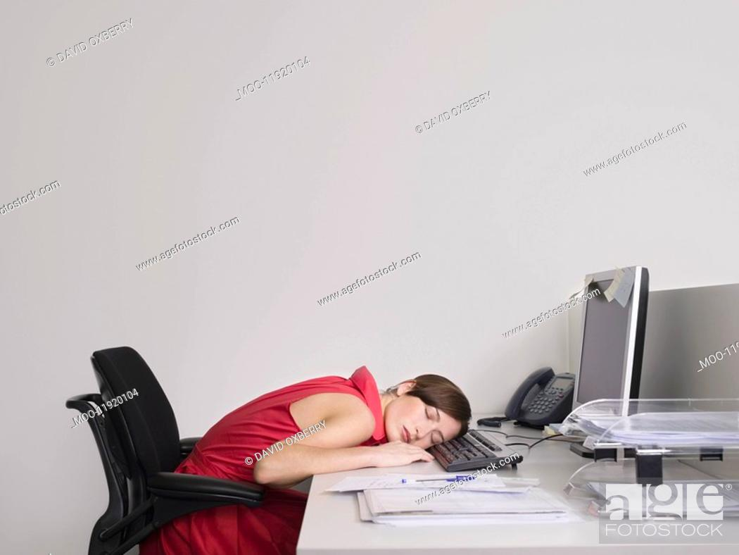 Stock Photo: Female office worker asleep at desk in office.