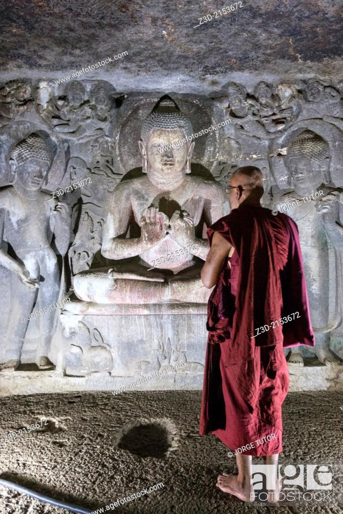 Imagen: Buddhist monk in front of a sculture of Buddha in preaching attitude. on Cave 6th. Ajanta Cave. UNESCO World Heritage Site, near Jalgaon, Maharashtra, India.