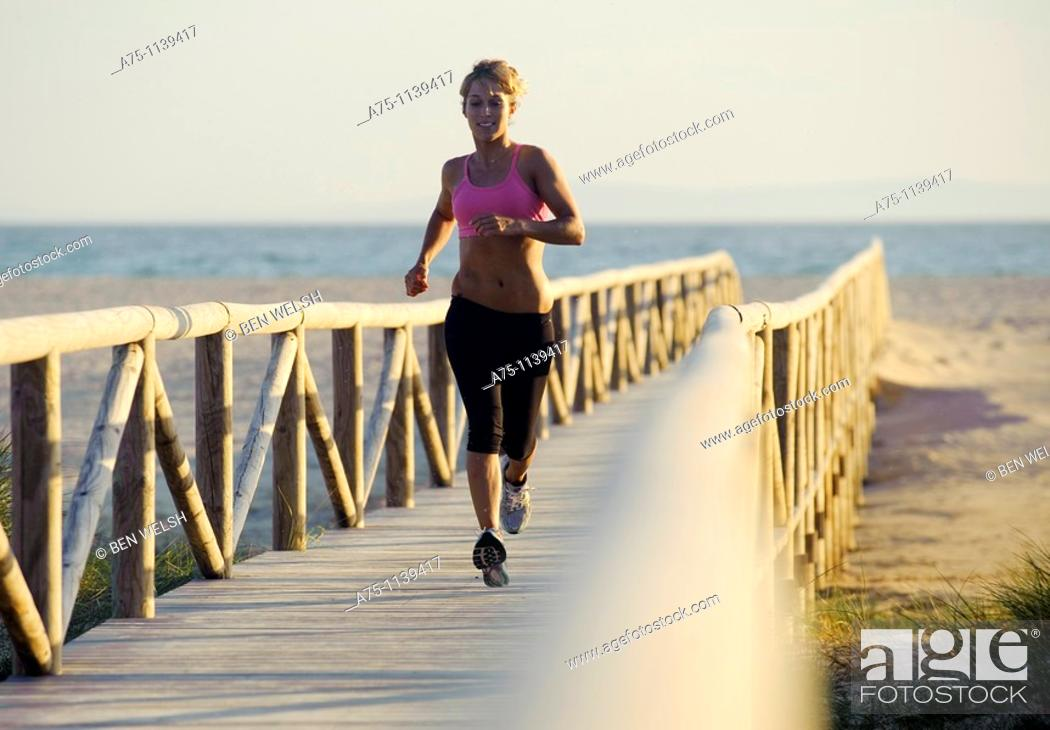 Stock Photo: Woman jogging on boardwalk.