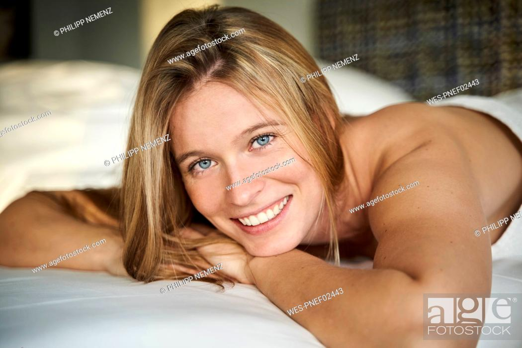 Stock Photo: Portrait of happy blond young woman lying in bed.