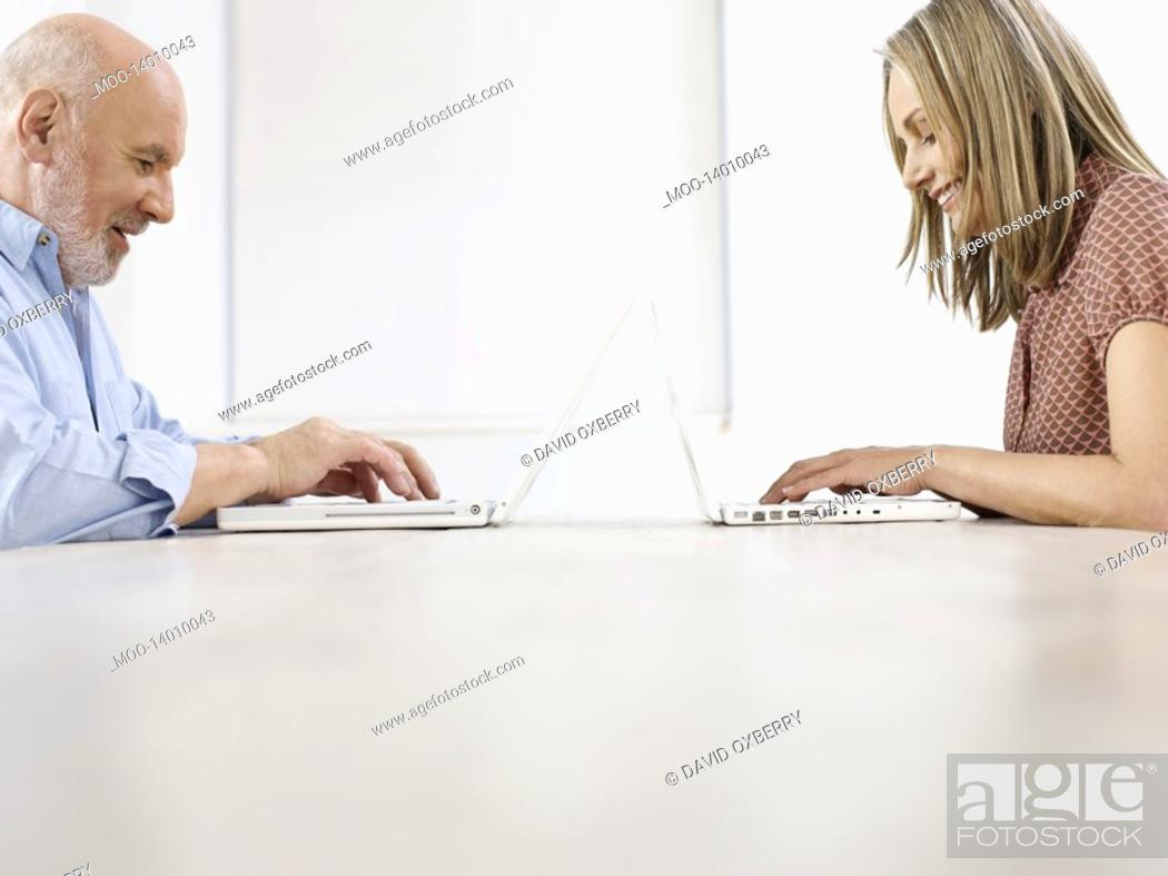 Stock Photo: Middle-aged man and mid-adult woman sitting opposite to each other using laptops profile.
