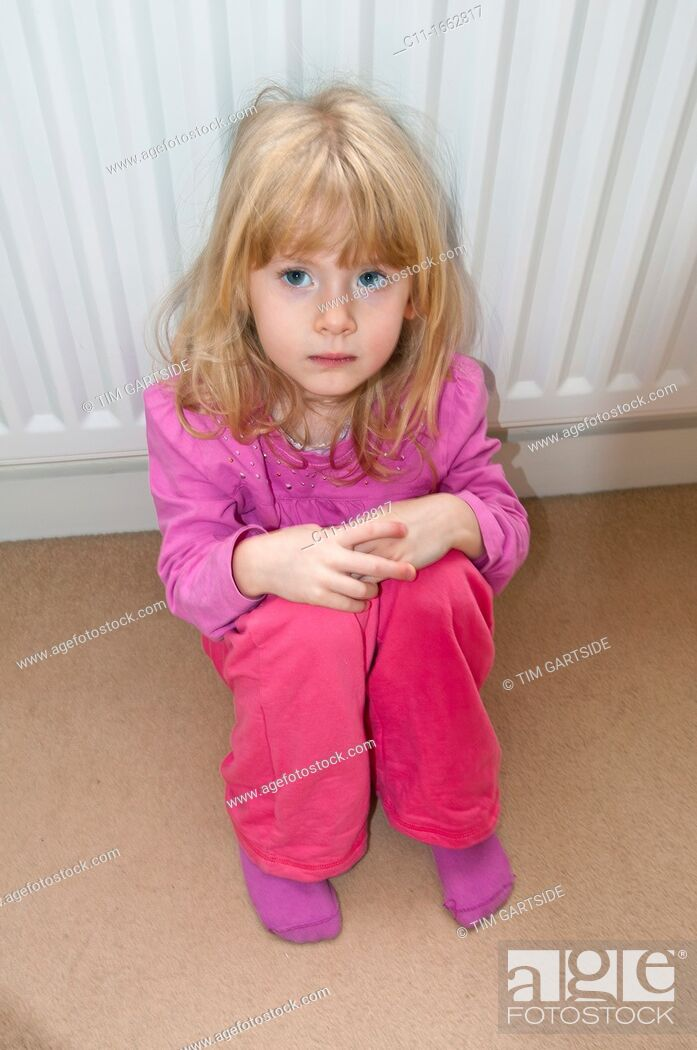 Stock Photo: young girl sitting on floor looking worried.