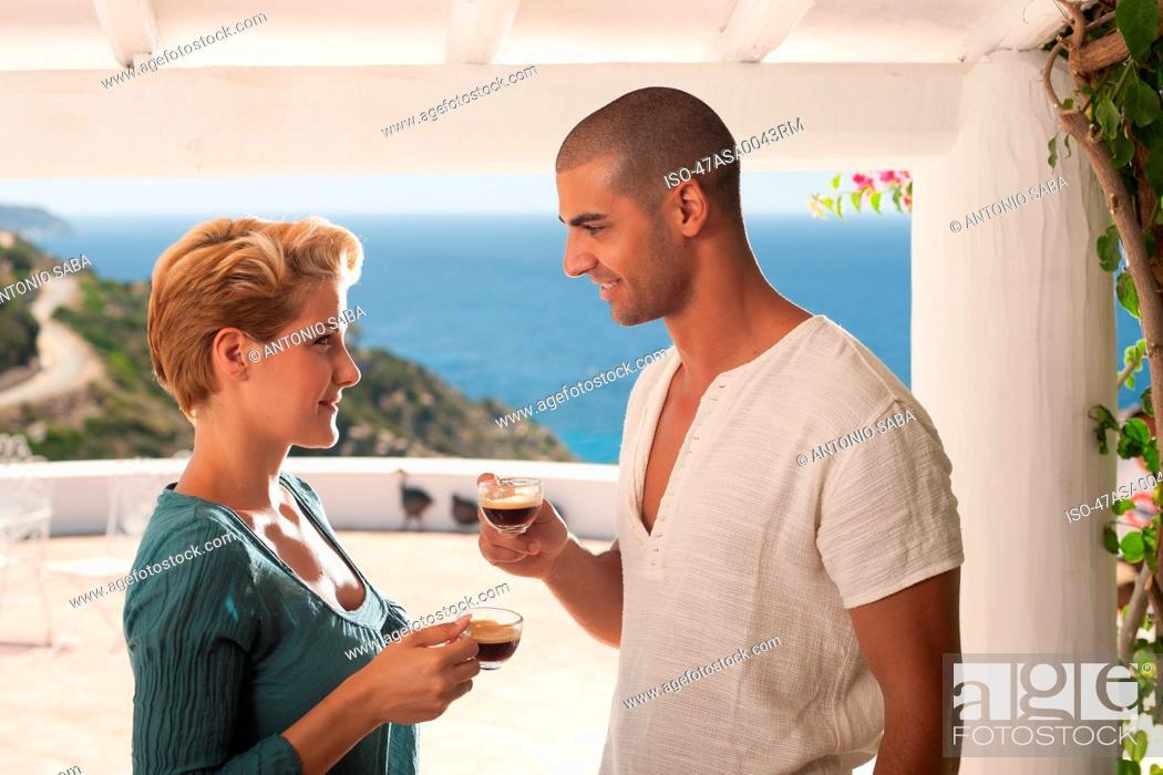 Stock Photo: Couple drinking coffee on balcony.