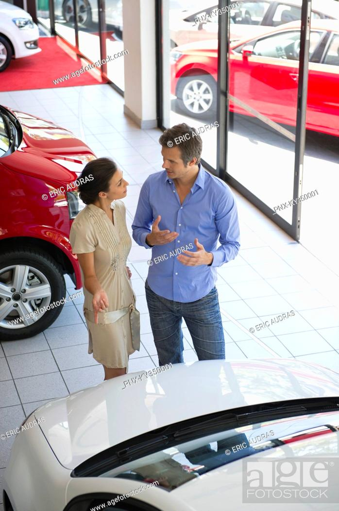 Stock Photo: Female salesperson showing car to mid adult man in showroom.