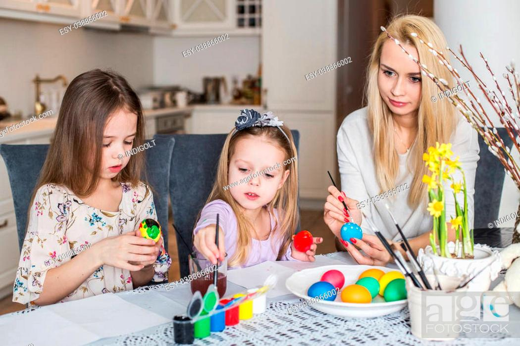 Stock Photo: Young mother and her two daughters painting Easter eggs. Cozy home atmosphere. Easter.