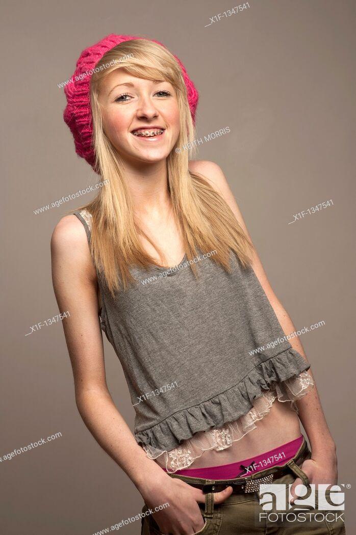 Stock Photo: A slim blonde 14 year old teenage girl with dental braces on her teeth, UK.
