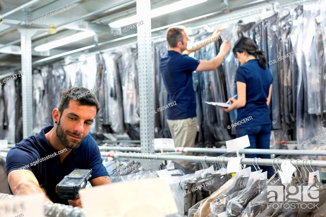 Stock Photo: Three warehouse workers preparing garments in distribution warehouse.