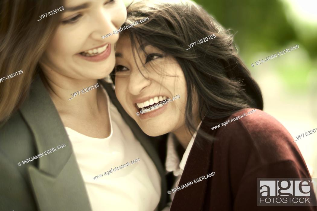 Stock Photo: smiling woman leaning against shoulder of friend, in Frankfurt, Germany.