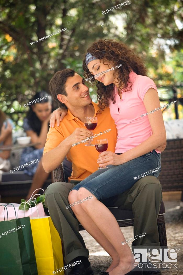 Stock Photo: Woman sitting on man's lap with shopping bags in cafe.