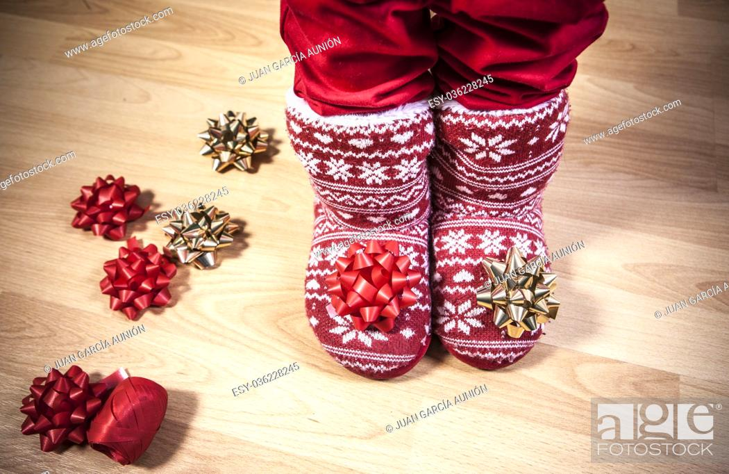Stock Photo: Red knitted boots with fur full of ribbons over wooden floor. Christmas staff concept.