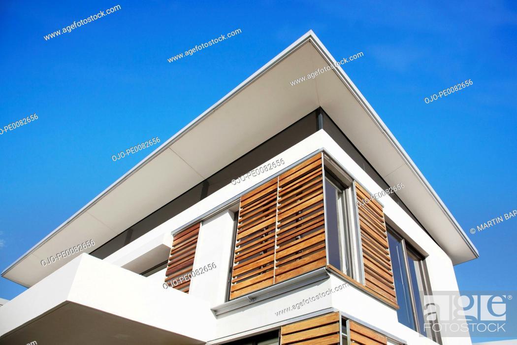 Stock Photo: Low angle view of wood shutters on modern house.