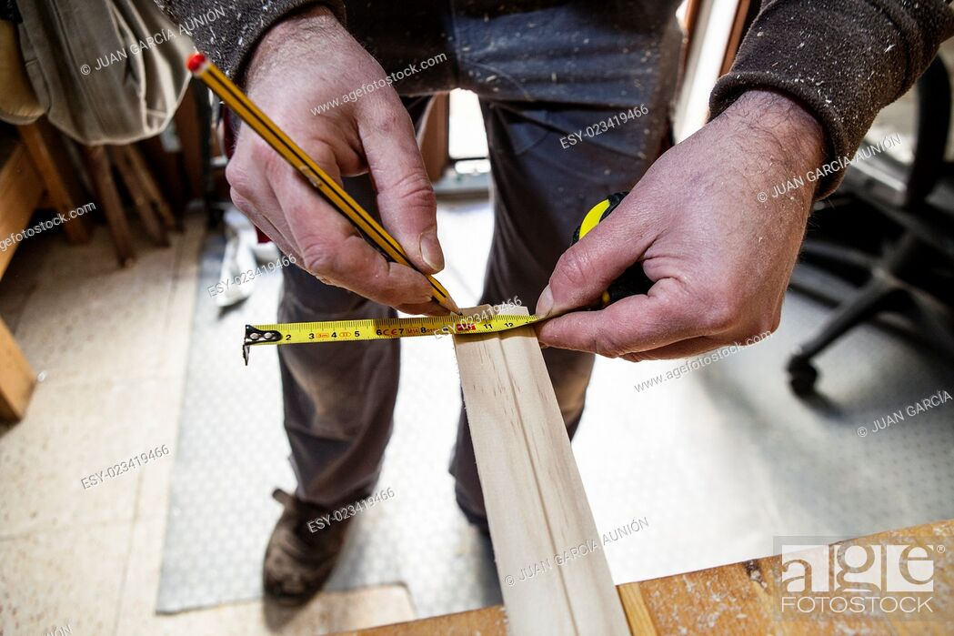 Stock Photo: Carpenter working with doorjambs. He is measuring wood and marking with pencil.