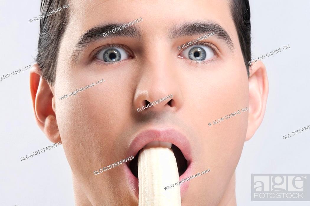 Stock Photo: Portrait of a man eating a banana.
