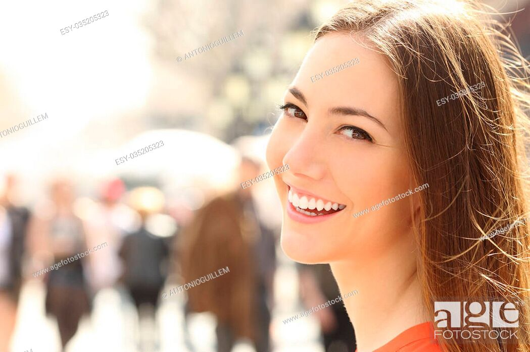 Photo de stock: Woman face smile with perfect teeth and smooth skin looking you on the street.