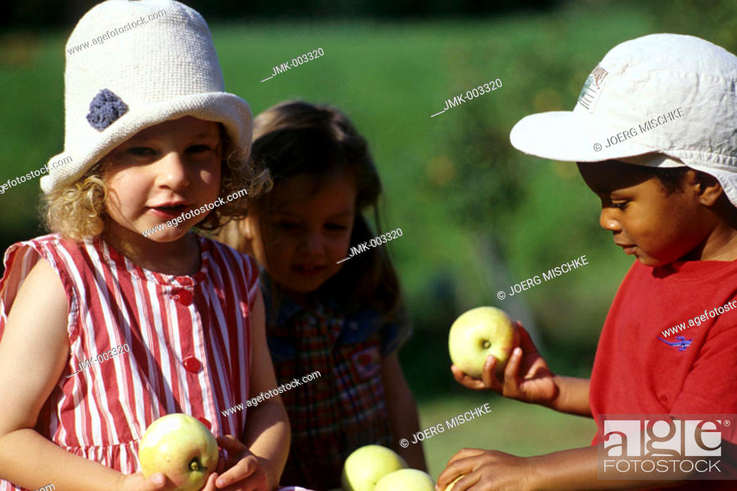 Stock Photo: Three little children, a boy and two girls, 1-5 years old, in the garden in summer.
