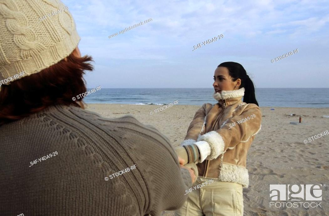 Stock Photo: Young Man holding a darkhaired Woman crossover by her Hands - Motion - Fun - Relationship - Trip - Season - Beach.