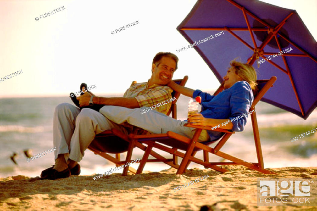 Stock Photo: Mid adult couple sitting on lounge chairs on the beach.