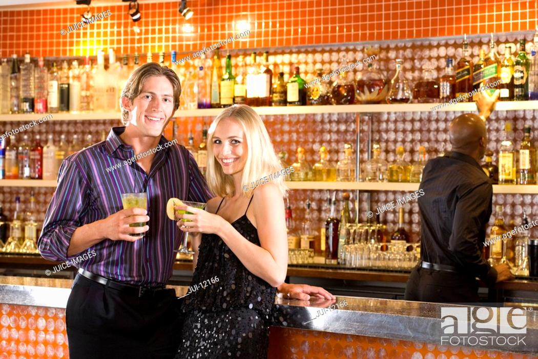 Stock Photo: Young couple at bar with drinks, smiling, portrait.