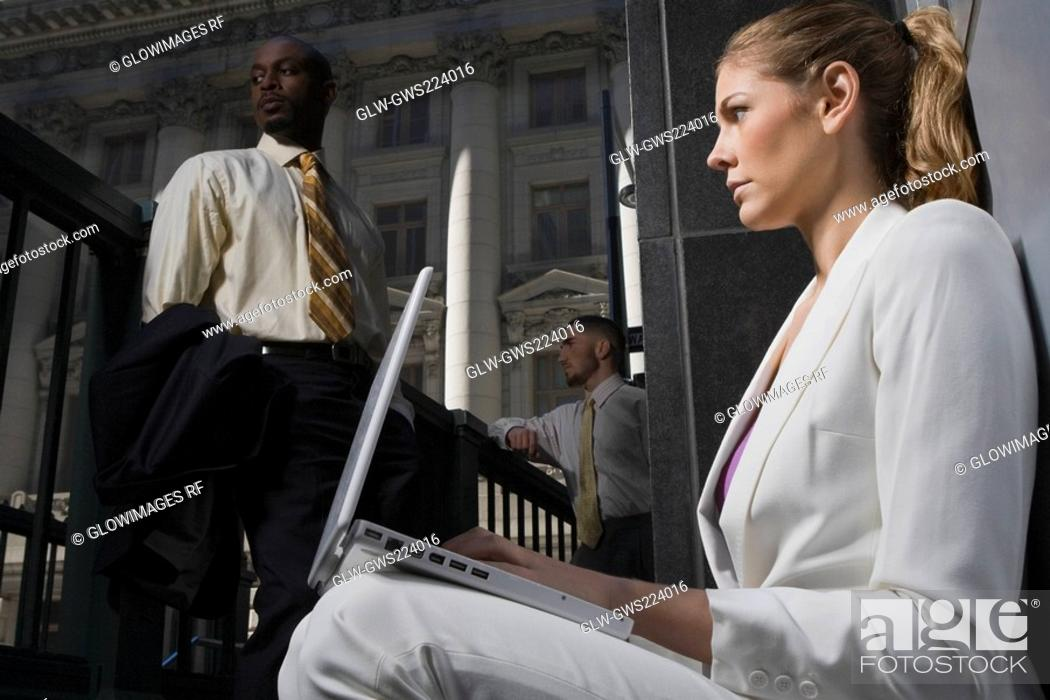 Stock Photo: Side profile of a businesswoman using a laptop with two businessmen in the background.