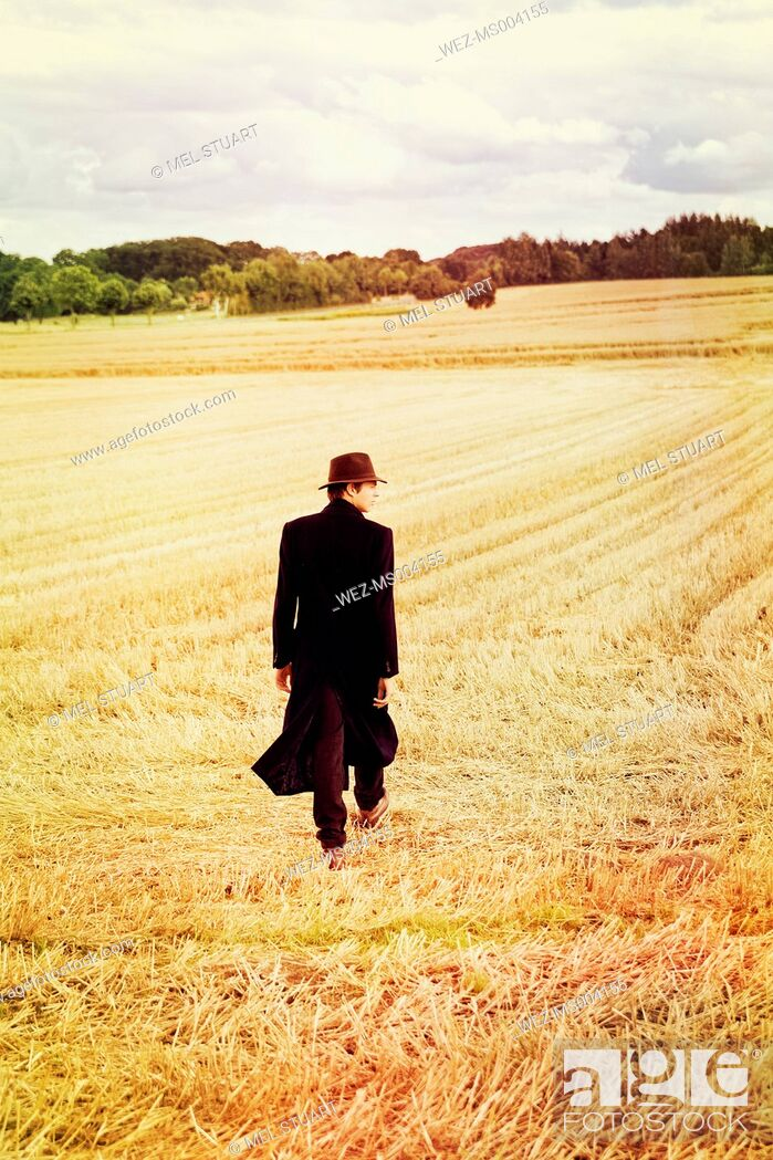 Stock Photo: Teenage boy with hat and coat walking on stubble field.
