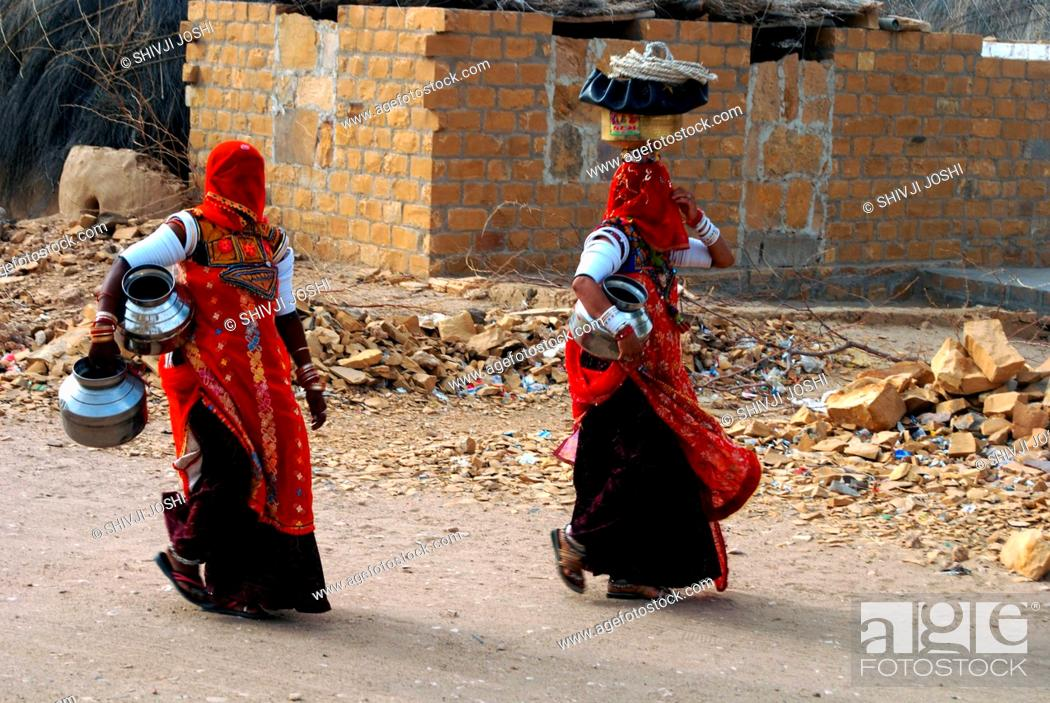 Stock Photo: Two Rajasthani Marwari village women with pots going to well to fetch water ; Khuhri ; Jaisalmer ; Rajasthan ; India NO MR.