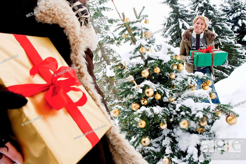 Stock Photo: Austria, Salzburg County, Couple holding christmas gift in snow.