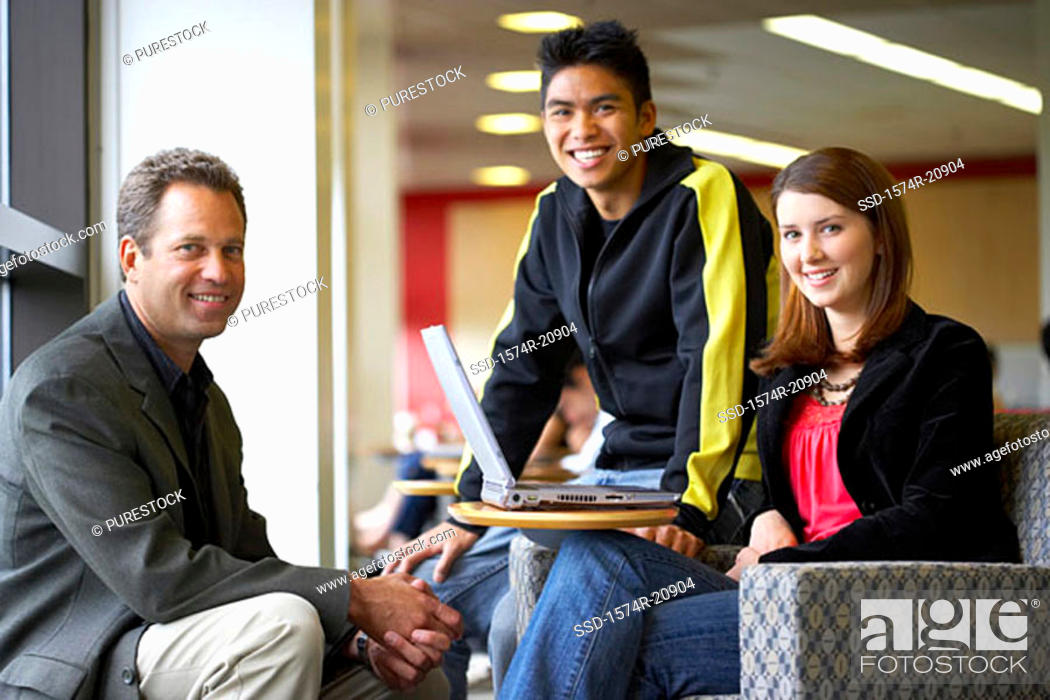 Stock Photo: Portrait of a professor sitting with his students and smiling.
