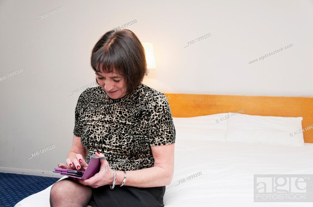 Stock Photo: Older woman using touchscreen tablet phone in hotel room.